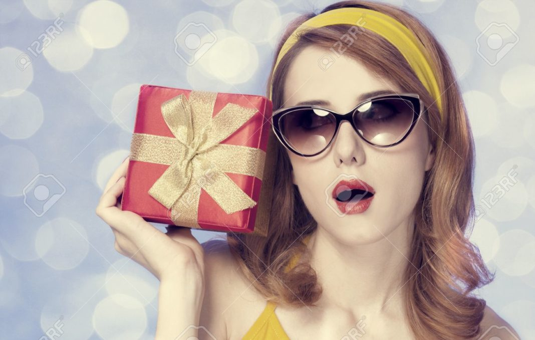 16660461-american-redhead-girl-in-sunglasses-with-gift-photo-in-60s-style-stock-photo